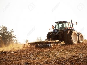 6276697-a-tractor-tilling-soil-in-a-field-stock-photo